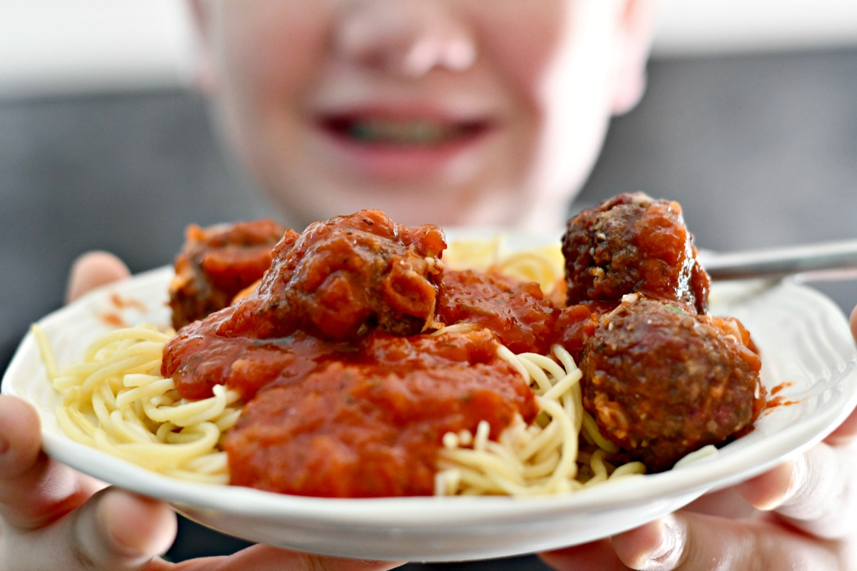 easy air fryer Parmesan meatballs close up on a plate with spaghetti