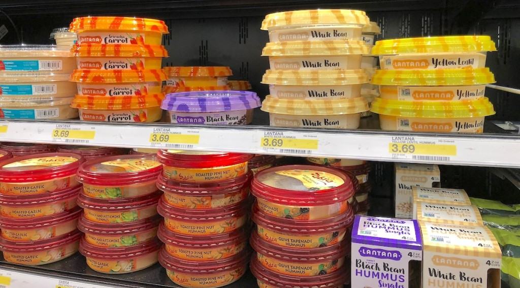 different flavors of hummus stacked on store refrigerator shelf