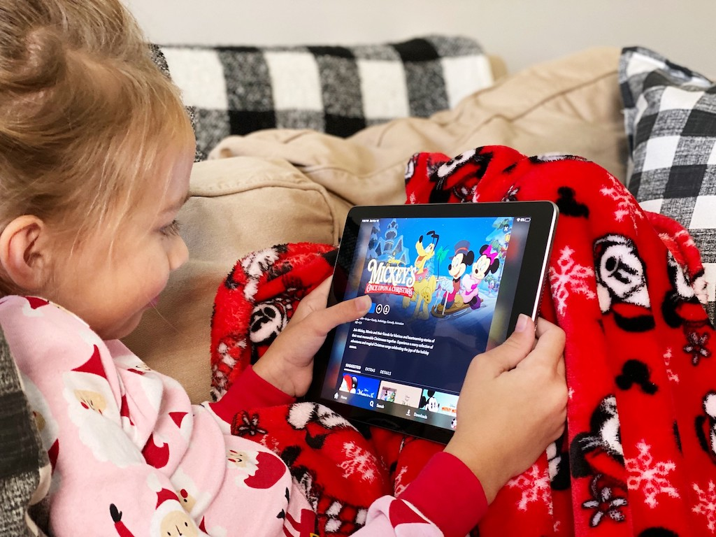 little girl watching disney movie on iPad with Mickey Mouse blanket