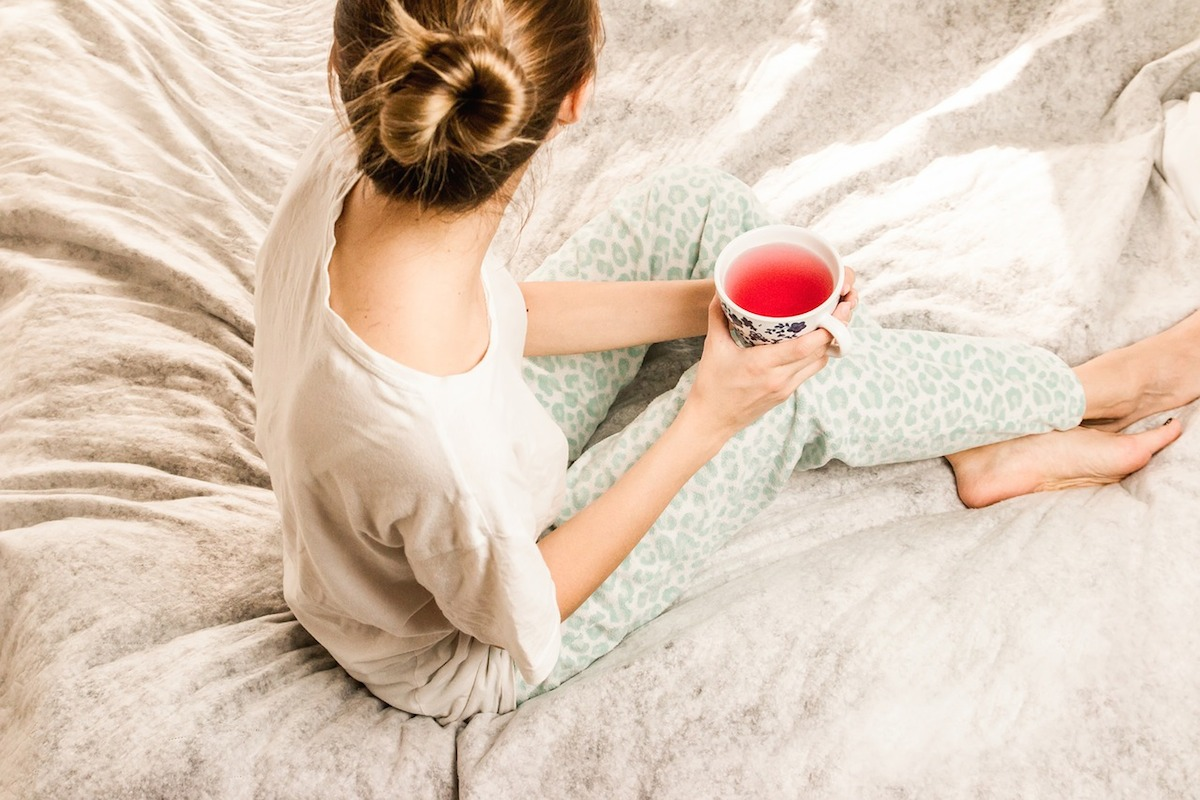 woman waking up in the morning enjoying drinking a cup mug of tea