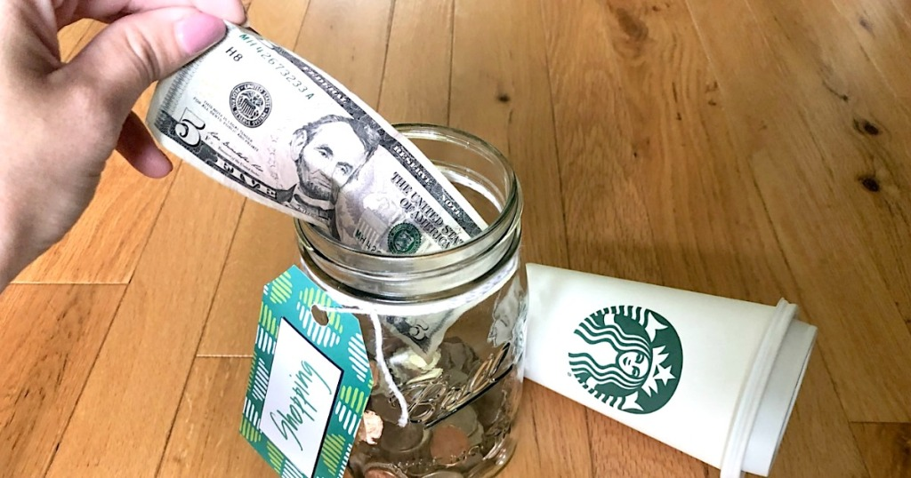 putting $5 bill in shopping money jar with Starbucks cup on the side