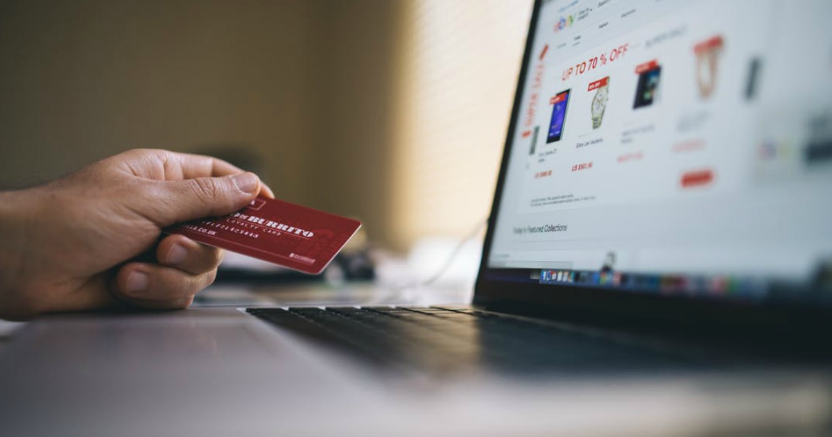 a credit card held next to an open laptop