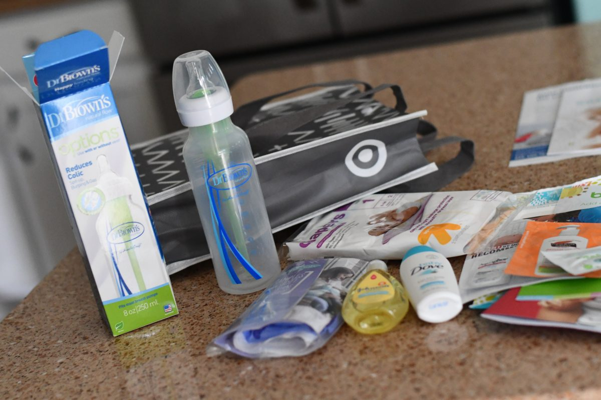 Target baby registry bag with bottle, sample size products, gift bag, and coupons.
