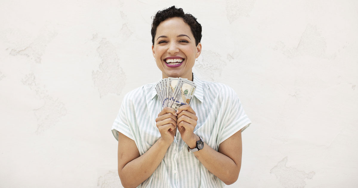 woman holding fanned out money and smiling