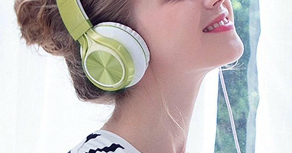 woman listening to green headphones