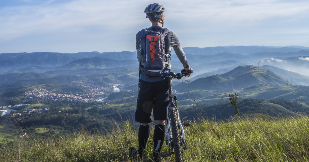 Man looking at view holding onto bike
