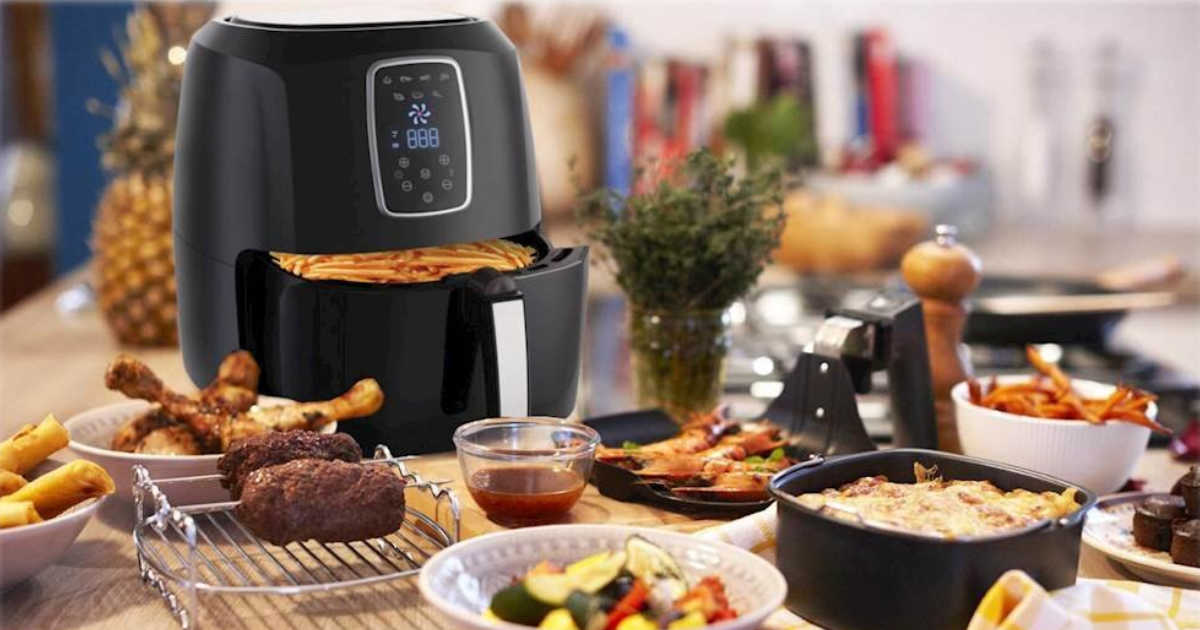 air fryer with fries in basket and a ton of food on the table
