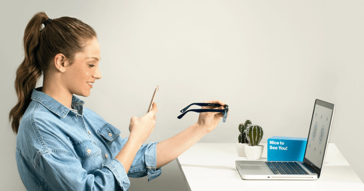woman taking a picture of her glasses with a smartphone