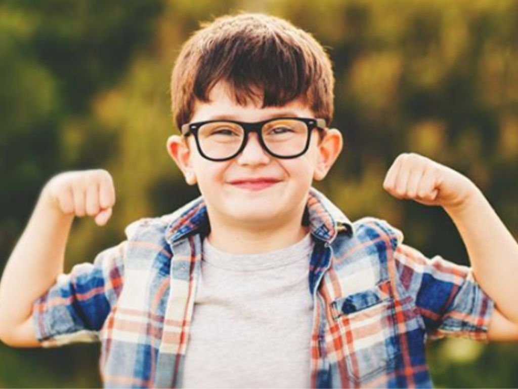 Boy smiling wearing glasses and showing muscles
