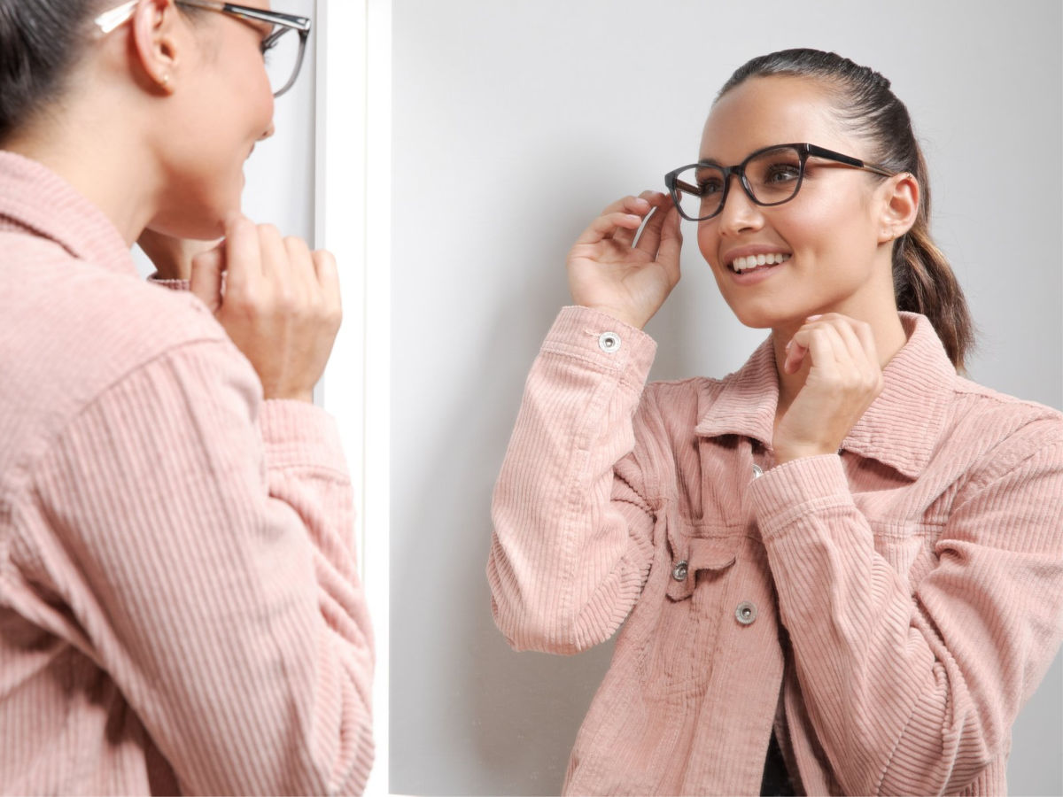a woman trying on glasses in the mirror