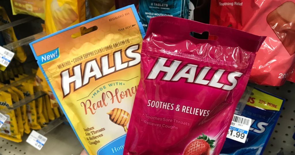 Hand holding cough drops in front of shelf