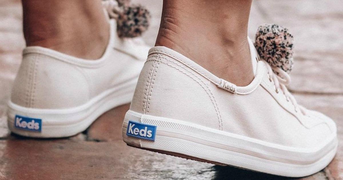 feet wearing light pink keds shoes