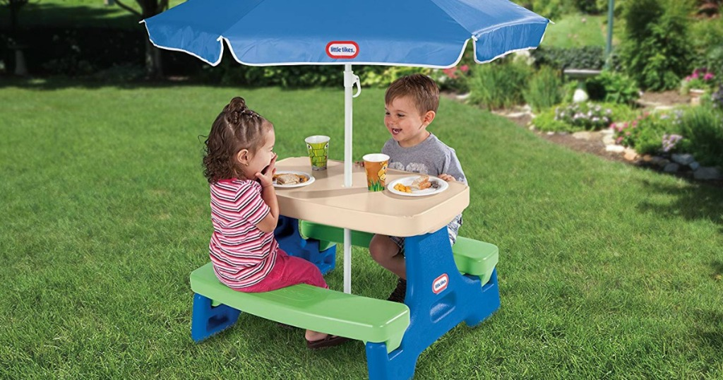 two kids sitting at a plastic table with umbrella