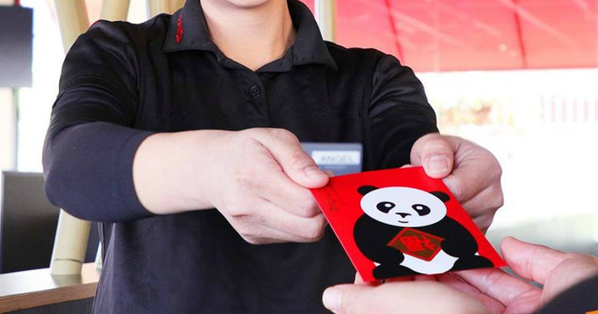 someone handing a red envelope to another person