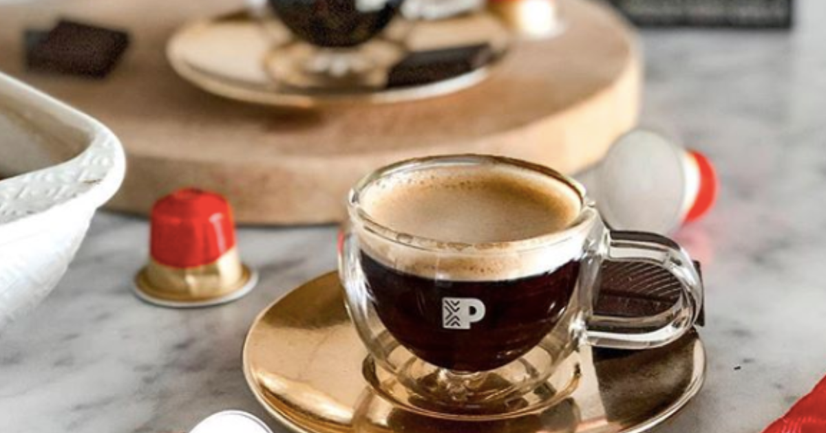 cup of Peet's coffee on a table with coffee pods