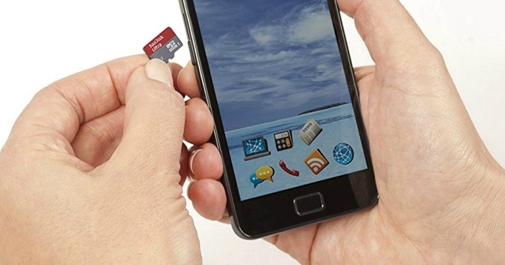 man holding a SanDisk memory storage chip and putting it into a smartphone
