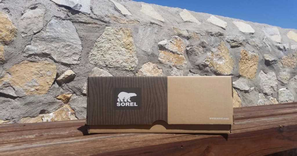 sorel shoe box on wood bench with rock wall in background