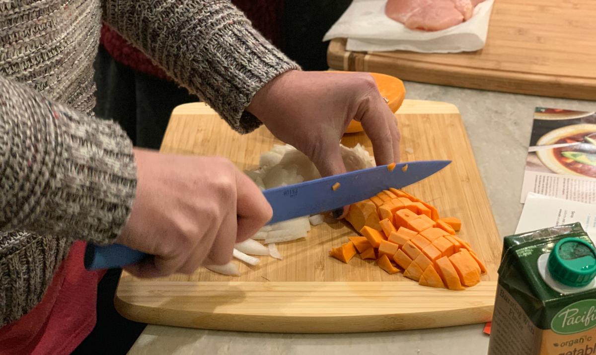 cutting sweet potatoes on a cutting board