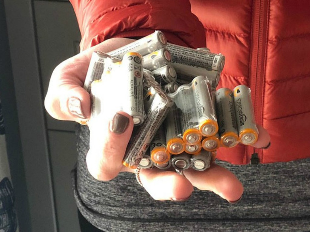 woman hand holding amazonbasics batteries
