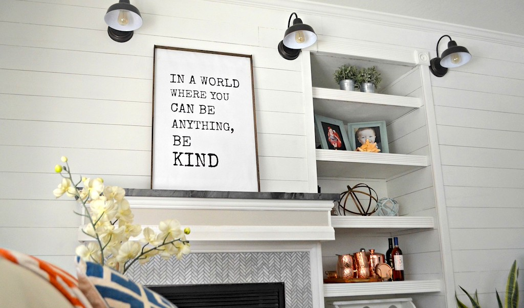 be kind sign above mantle in living room