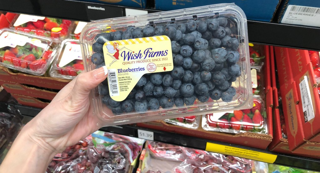 hand holding fresh blueberries with cartons of strawberries in the background