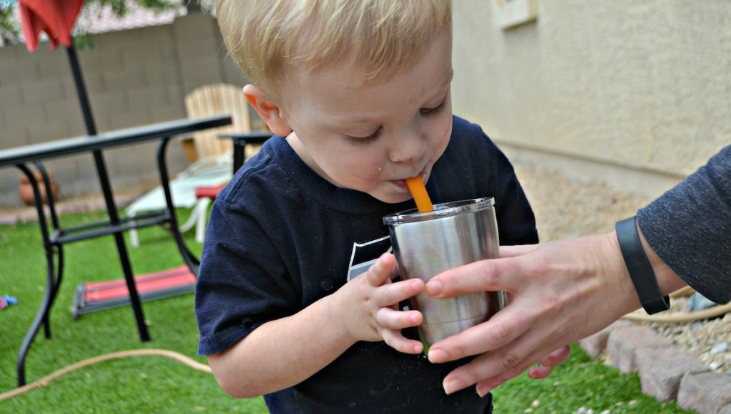boy drinking water outside with parent holding stainless steel mug cup