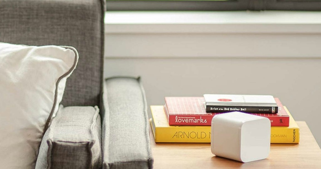 The Circle sitting on an end table with books on it as well next to a couch