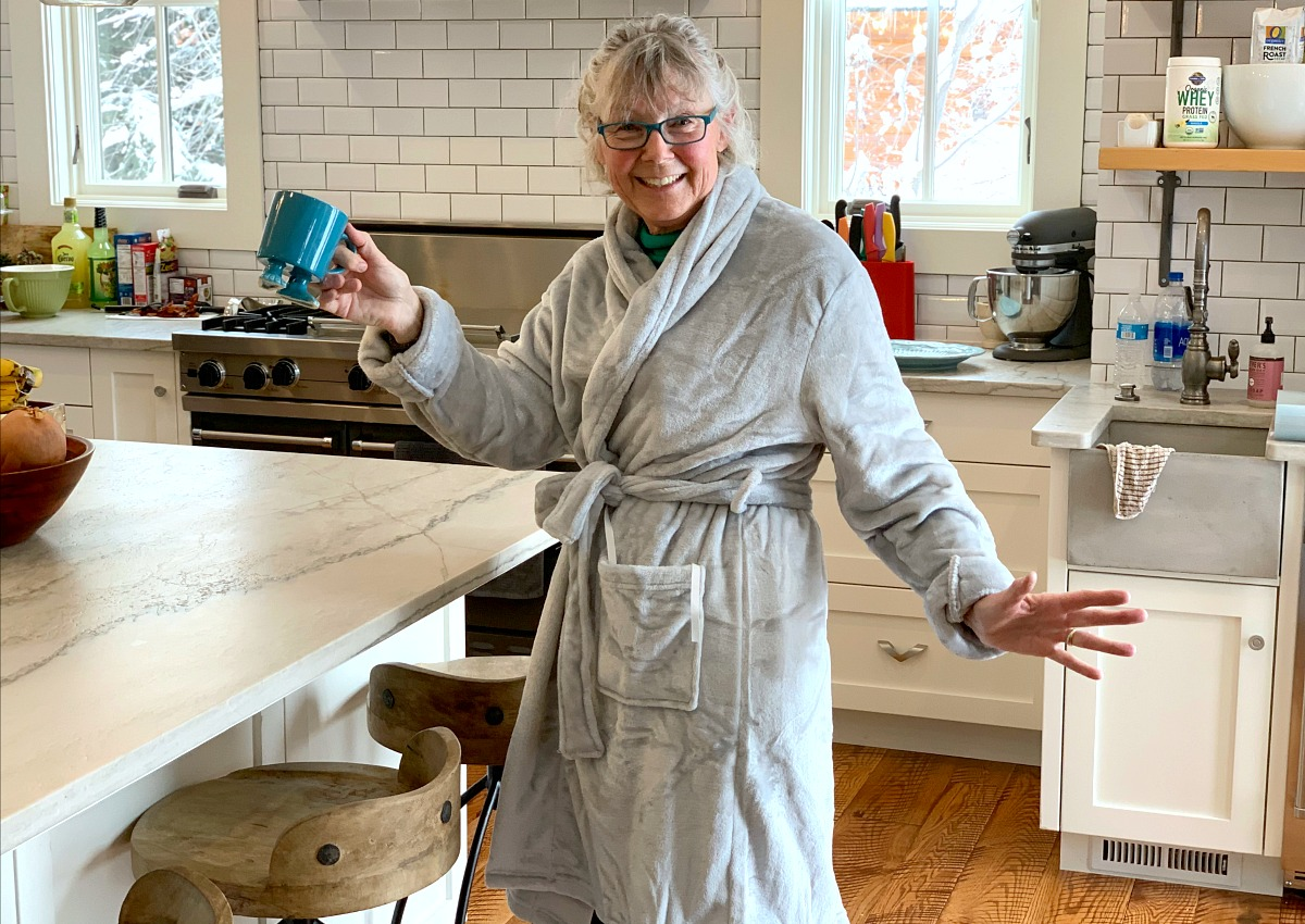 collin's mom wearing plush bathrobe and holding coffee mug