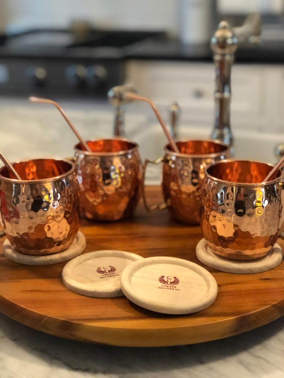 copper mugs with straws on wood tray
