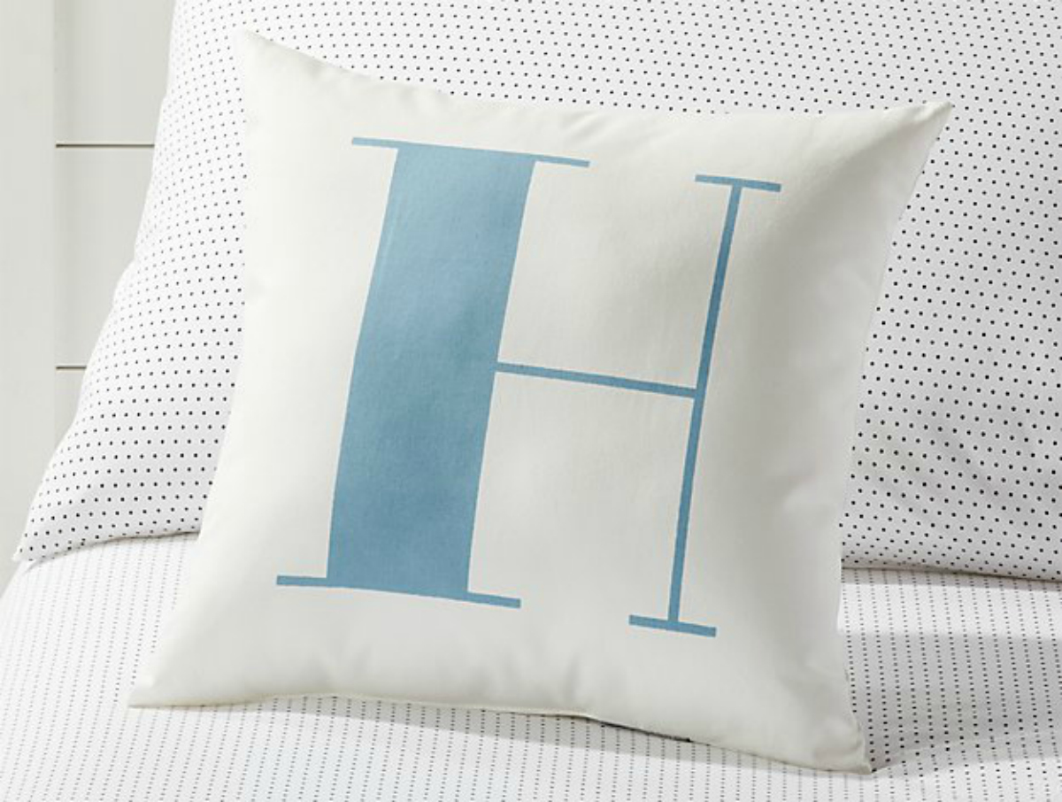 blue and white letter H pillow sitting on bed with sheets