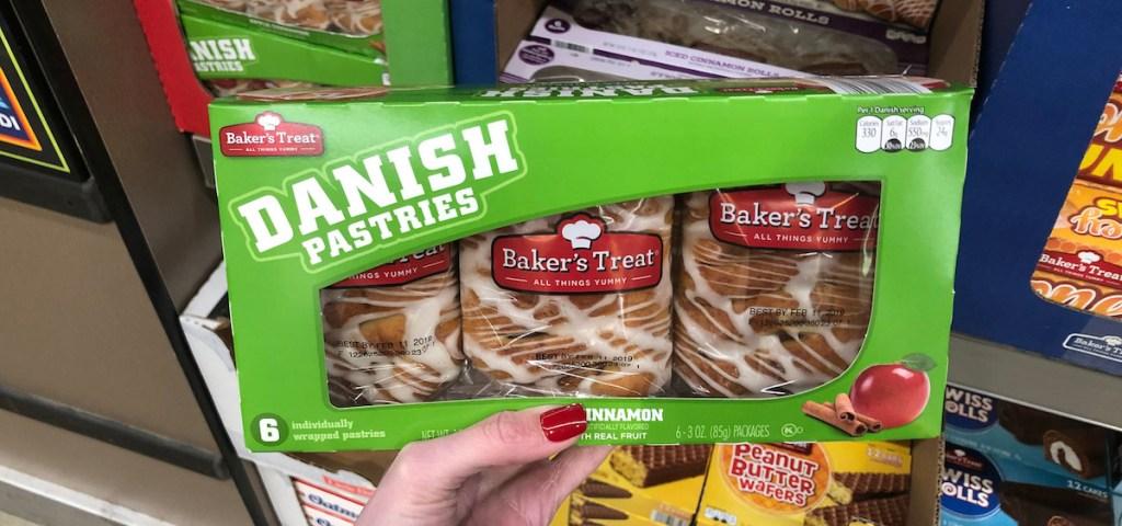 hand holding a green box of apple cinnamon danish pastries