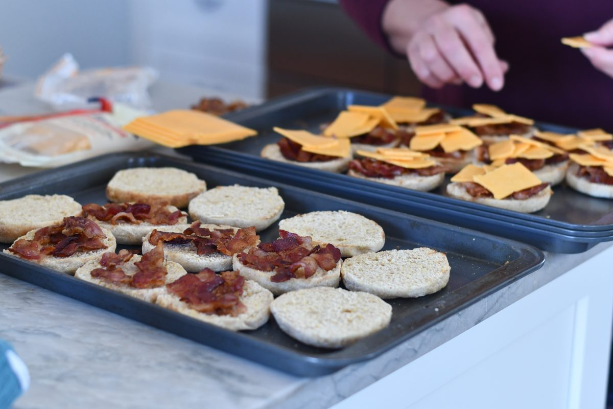 melted bacon and tomato english muffins on a baking sheet