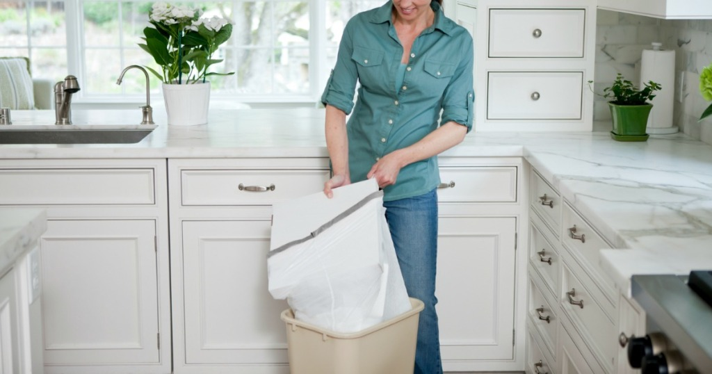 woman filling a garbage bag in a kitchen