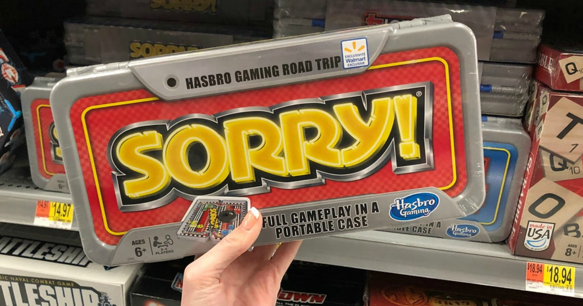hand holding sorry travel game in front of store shelf