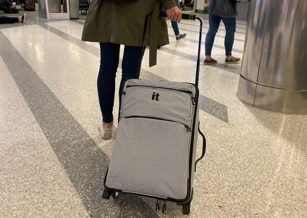 woman walking in airport pulling gray it carry on luggage