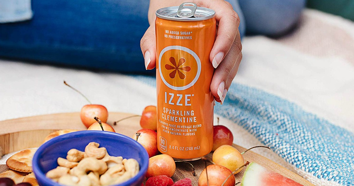 hand holding an orange can of IZZE sparkling fruit juice on a tray with food