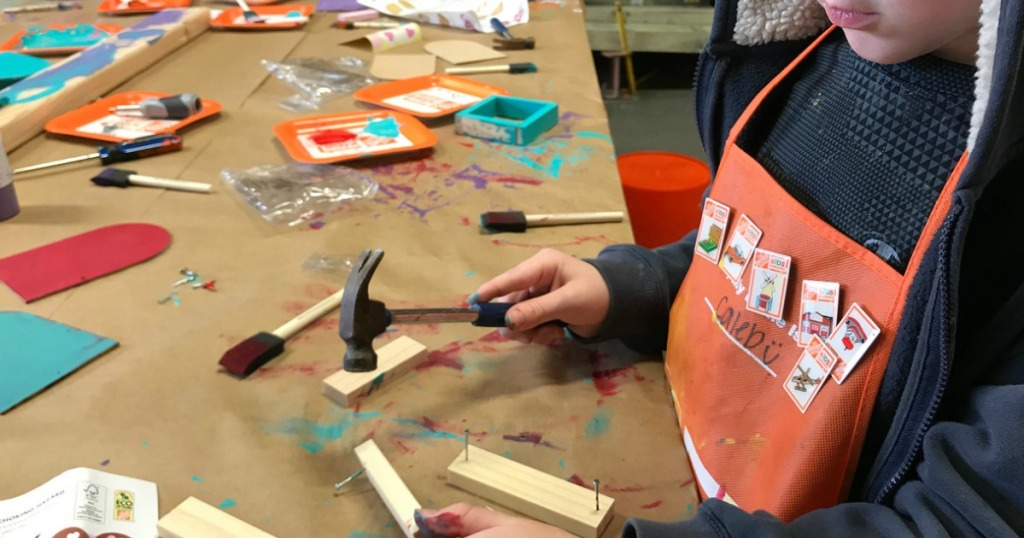 child holding hammer building with wood, nails, paint and brushes