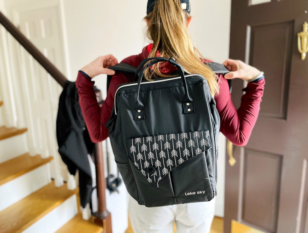 woman putting on black travel backpack in front of doorway and stairs