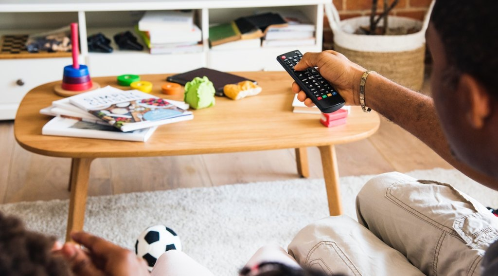 man holding a remote with coffee table in the background with magazines and messy toys