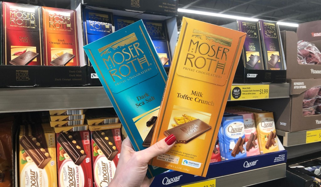 hand holding two moser roth chocolate bars with chocolates in the background
