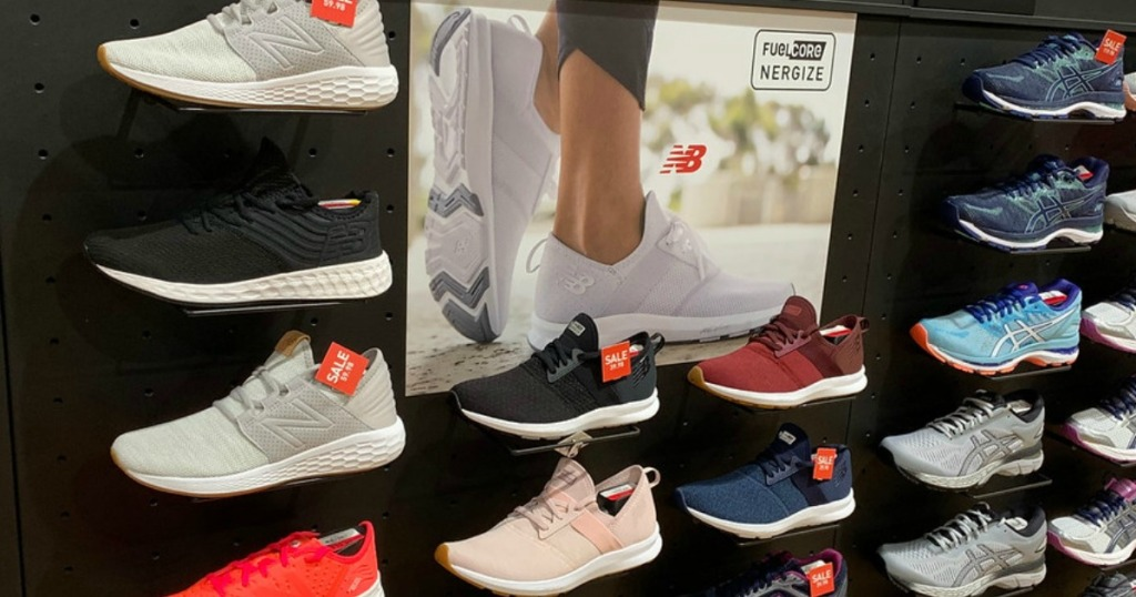Various women's New Balance shoes displayed on a wall in-store
