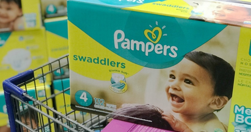 Large box of pampers swaddler sitting on top of a shopping cart