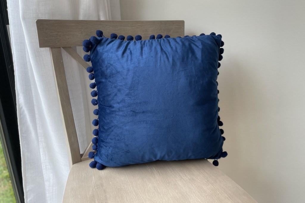 pom pom pillow on chair