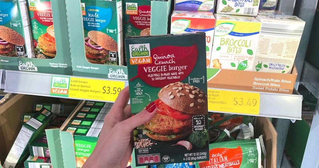 hand holding a box of veggie quinoa burgers in frozen aisle