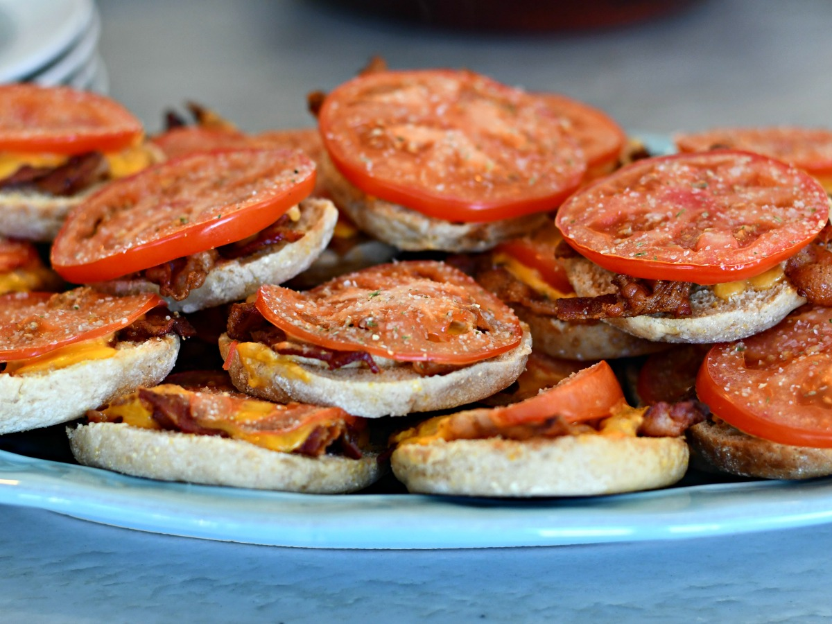 easy bacon and tomato baked english muffins stacked on a serving tray
