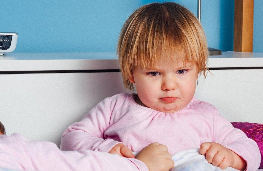 sad toddler girl sitting on bed wearing a pink shirt