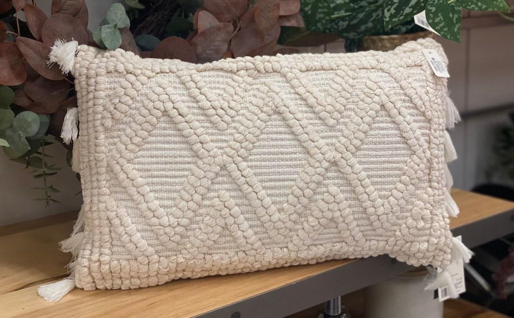 close up of textured cream lumbar throw pillow on wood shelf