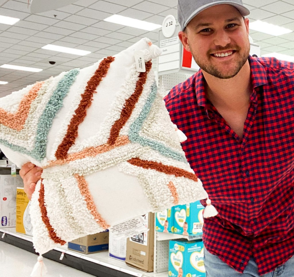 man holding colorful throw pillow in target store