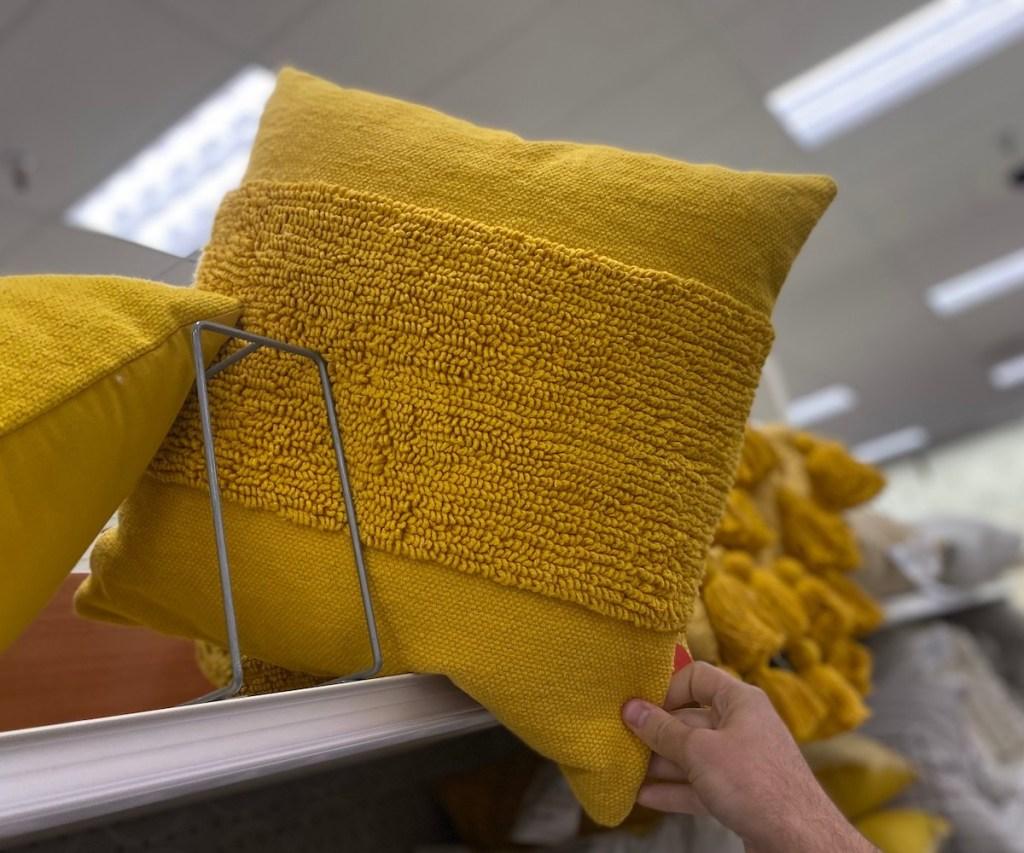 hand pulling mustard yellow throw pillow off store shelf