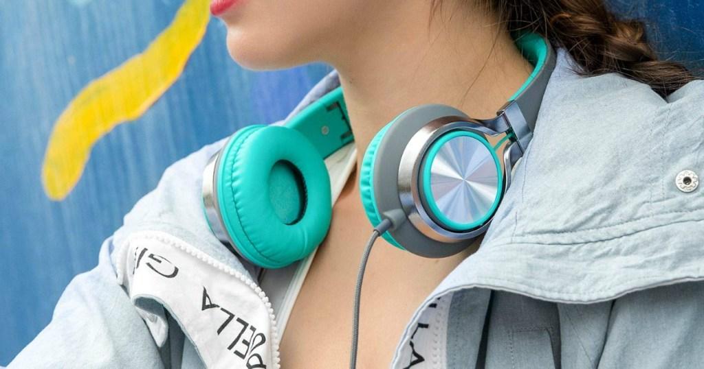 woman with headphones resting around her neck